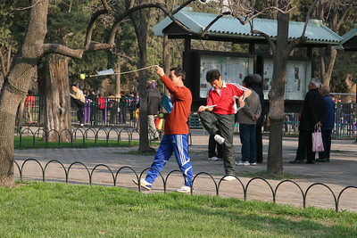 A little martial arts in the park;  the guy on the left has a version of chain-whip, and the guy on the right is working with nunchucks.