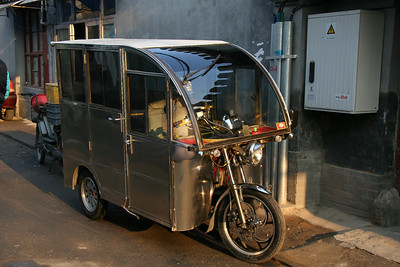 The mighty tuk-tuk lives on in China as well!  The ones in Beijing are shiny and new, but the principle hasn't changed (make a car from a motorcycle)