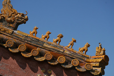 All roof corners are protected by the set of figurines, leading the charge, always, a man riding a chicken, followed by a number of small dragons (dogs?) and one good sized dragon, presumably just in case.