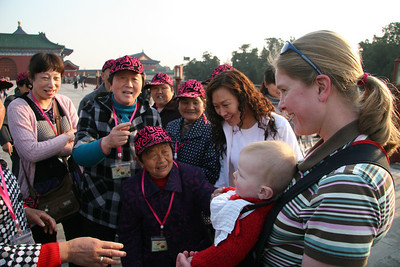 """The more cosmopolitan Beijingers weren't that interested in Sebastian, but the tour groups (i.e. the folks from the distant country side) were sometimes VERY excited.  Note that grandma in this group is """"shorter"""" than Sebastian! After I took this picture Gretchen was pulled in for a """"family group shot""""."""