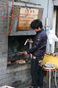 More street food; in this case some sort of skewered meat, and if the coals aren't hot enough, the hair dryer is used to augment....