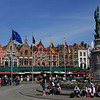 Pretty buildings, statue and tourists in the square in Bruge.