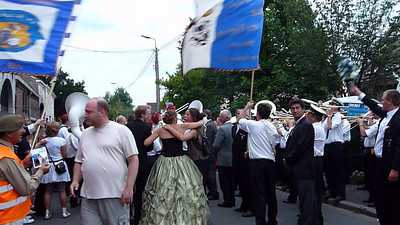 Herrmalle.There are two bands in town marching back and forth on the main street, representing the blue and the red. When the bands intercept, they continue to play their own tune as loudly as possible, while marching right through the other band.