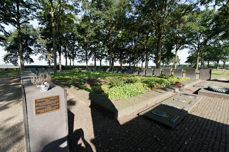 "Bruges / Ypres - Langemark German Cemetery.  The photo shows the ""Kameraden Grab"" (grave) which is a Crypt underneath the green area in the foreground.  Approximately 25,000 German soldiers (and two English soldiers) are interred in the Crypt.  The pillars around the edge have metal plates mounted on them which contain the names of those that could be identified."