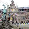 The building behind the fountain is the City Hall or Stadhuis.  It displays the flags of many different countries, to emphasize the importance of international trade to the city.  On the central tower can be seen the coats of arms of the great medieval powers that shaped the city:  the lion of the Duchy of Brabant,  the Margraviate of Antwerp, and the two-headed eagle of the Habsburgs.  I will get back to you with more detail after I read up on my European history.