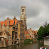A small boat passes by beautiful old buildings in Bruges, Belgium