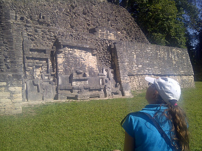 Gazing at the Mayan pyramid just before realizing she sat down on a fire ant nest