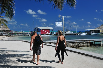 © Joseph Dougherty. All rights reserved.  Divers walking along the waterfront in San Pedro, Ambergris Caye, Belize.