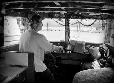 "Captain Fred Dorsey, a commercial fisherman at the helm of his vessel ""Marjorie"", enroute to the Talheo Cannery."