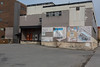 Former Ontario Intelligencer newspaper building, rear wall, with posters of news stories.
