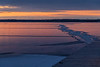 Bay of Quinte before sunrise. Lines in the ice and footprints close to shore.