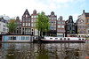 Many of the buildings in Amsterdam, at least along the canals, are leaning one way or another. The buildings are built on wooden pilings sunk into the wet ground. They are build leaning into each other for additional strength. Most of the buildings along the canals are narrow. The width of the front of the house indicated the wealth of the owner. Also note the different house boats.<br /> _MG_7357