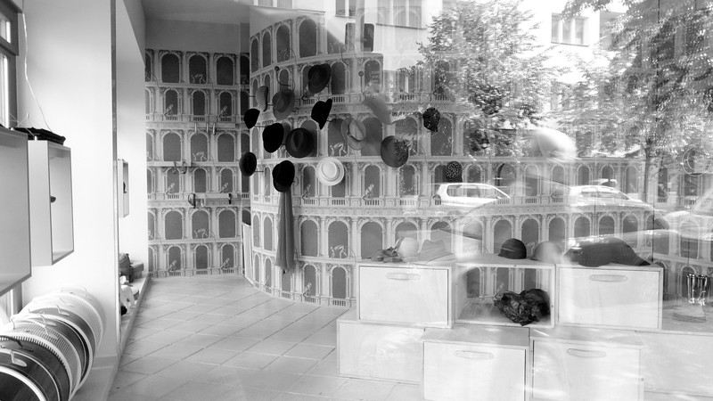 A hat store photographed through the front window.