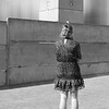 A young girl lights a cigarette in front of one of the last standing guard towers at the Berlin Wall.
