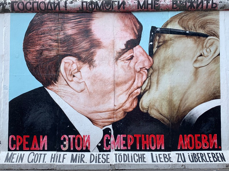"""The """"Fraternal Kiss"""" by Dimitri Vrubel.  Here, we see the DDR and USSR leaders (Honecker and Brezhnev) exchanging quite the kiss, with the words """"Dear God, help me to survive this deadly love"""" written underneath."""