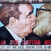 "The ""Fraternal Kiss"" by Dimitri Vrubel.  Here, we see the DDR and USSR leaders (Honecker and Brezhnev) exchanging quite the kiss, with the words ""Dear God, help me to survive this deadly love"" written underneath."