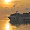 """Sunrise arrival, Bermuda.  The Norwegian cruise ship Dawn passes in the harbor channel by Saint George""""s Island."""