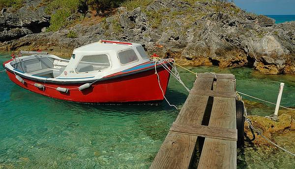 An old small fishing boat launch at the quay in a Bermuda small cove along north shore / Un vieux bateau de pêche au quai dans une petite baie abritée le long de la rive nord aux Bermudes.