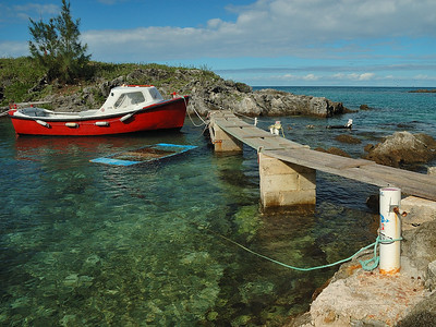 An old small fishing boat and a sink launch at the quay in a Bermuda small cove / Un vieux bateau de pêche et une chaloupe submergée au quai dans une petite baie abritée aux Bermudes.