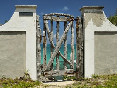 """""""North Shore Road"""" near Bailey's Bay, Bermuda/Bermudes: Sandymount East entrance. There is only the sea and rocks over the door. / Ça semble être l'entrée d'une propriété cependant il n'y a que la mer et des rochers de l'autre côté de la porte."""