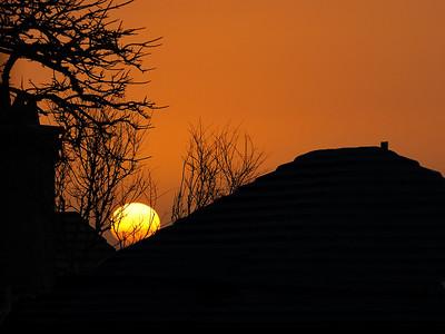 Bermuda; an orange sunset over white bermudian roofs / Coucher de soleil orange audessus de toits blancs caractéristiques des Bermudes.