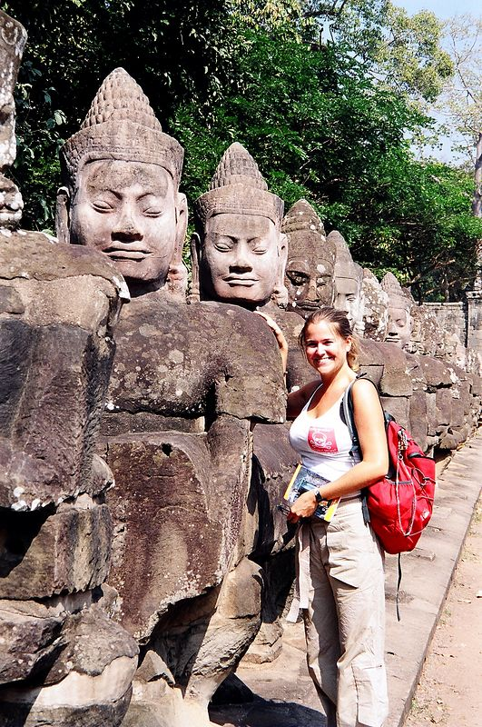 Me next to carved figures on bridge, Angkor.