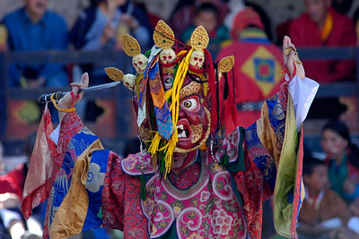 """Masked dance at the Paro Tsechu Festival of Dance held in Paro, Bhutan. This is the biggest and most spectacular Buddhist festival celebration.  The Paro Tshechu festival honors Guru Padmasambhava, """"one who was born from a lotus flower."""" This Indian saint contributed enormously to the diffusion of Tantric Buddhism in the Himalayan regions of Tibet, Nepal, Bhutan etc. The biography of Guru is highlighted by 12 episodes of the model of the Buddha Shakyamuni's life. Each episode is commemorated around the year on the 10th day of the month by """"the Tshechu.""""  During Tshechu, the dances are performed by monks as well as by laymen. The Tshechu is a religious festival and by attending it, it is believed one gains merits. It is also a yearly social gathering where the people, dressed in all their finery, come together to rejoice."""