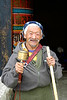 Old Buddhist man in Bhutan. Seen in the image is a prayer wheel which is rotated. Each rotation is considered a prayer said, so the people walk turning this prayer wheel around.