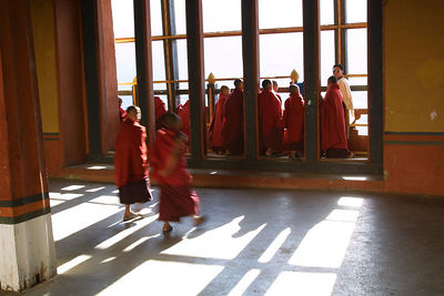 Monks peer out the window at the setting sun.