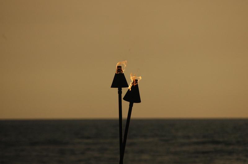 Tiki torches light the way at night.