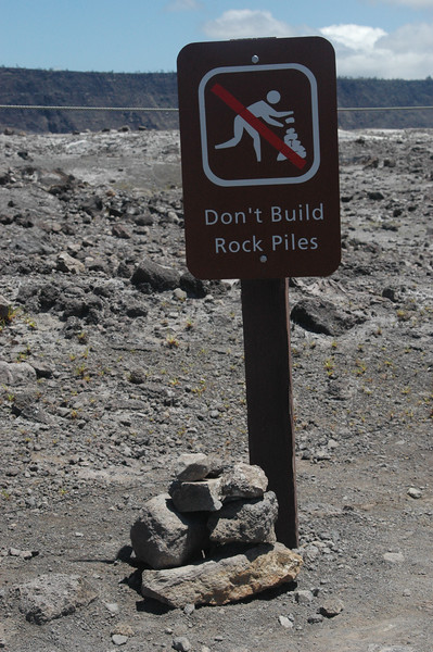 """Someone built a rock pile at the base of the sign that reads """"Don't Build Rock Piles"""""""