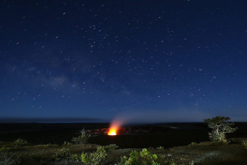 The stars pay their homage to the Halema'uma'u Crater glowing at night because of the boiling lava lake under it.