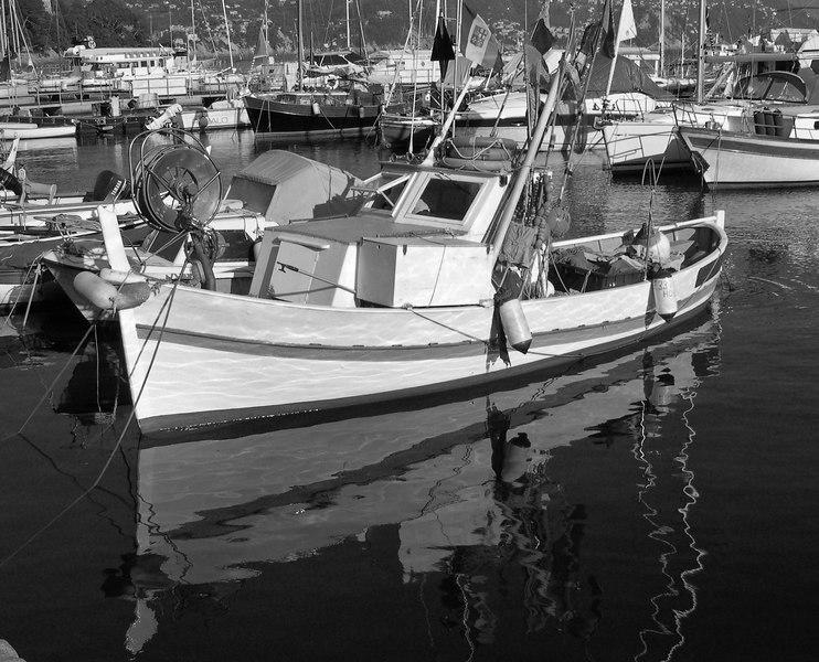 A fishing boat displays international flags - Santa Margarita Ligure - Italy