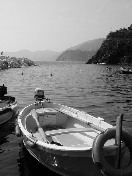 Traditional fishing boat sits in the clear Mediterranean waters of Cinque Terre - Monterosso - Italy