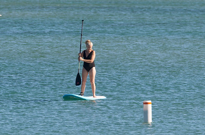A woman practices using her paddle board.