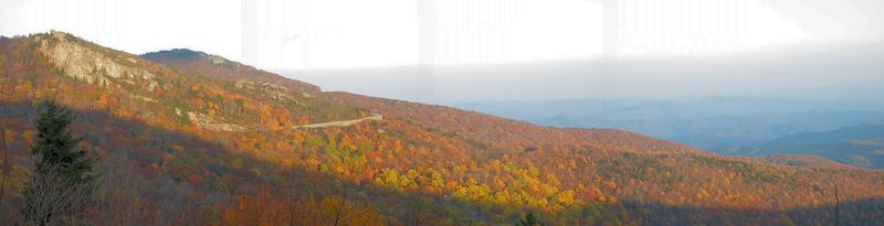Setting sun over fall view, including ribbon of Blue Ridge Parkway, near Blowing Rock [panoramic]