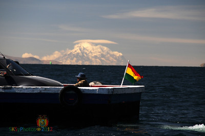 Carry ferry (really a 2-car raft) crosses the Tiquina Straits as Illimani seems to rise out of Lake Titicaca in the background.