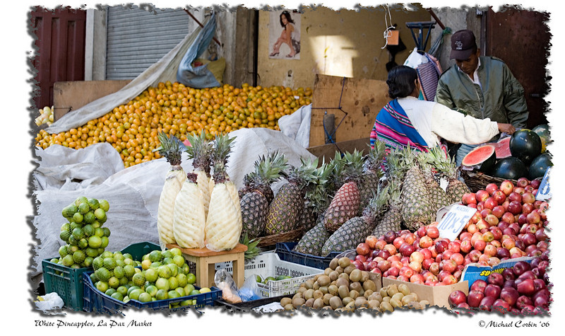 A fruit vendor in the markets of La Paz. Watermelons, apples, kiwis, lemons, limes, and or course pineapples on display.