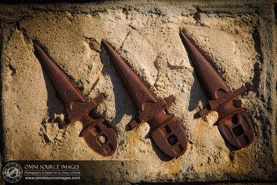 Rusted old farming tools embedded in concrete on a stone wall. Borges Ranch, Walnut Creek, CA.
