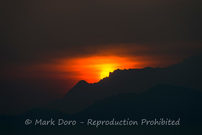 The sun rises over Mount Kinabalu, from Gaya Island, Malaysian Borneo