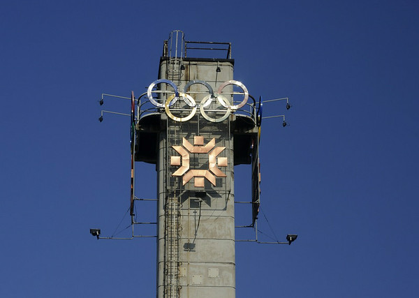 1984 Winter Olympics tower, Sarajevo, Bosnia-Hercegovina, 12 June 2014.  Communist Yugoslavia still existed when the 1984 Winter Olympics were held in Sarajevo.  The games are still remembered in Britain as the occasion when Jayne Torville and Christopher Dean won the ice dancing gold medal for their performance to the music of Ravel's Bolero.  Nobody then foresaw the ghastly fate which would befall Sarajevo less than ten years later.   (Photographed from inside a bus.)