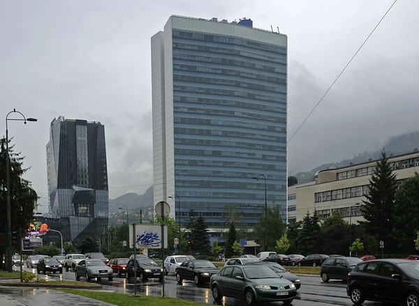 Parliament building, Ulica Zmaja od Bosne (Dragon of Bosnia Road, Sarajevo, Bosnia-Hercegovina, 13 June 2014.  Looking south east.  The building was set on fire during the siege and badly damaged.  The hills in the background were occupied by the besieging Serbs.