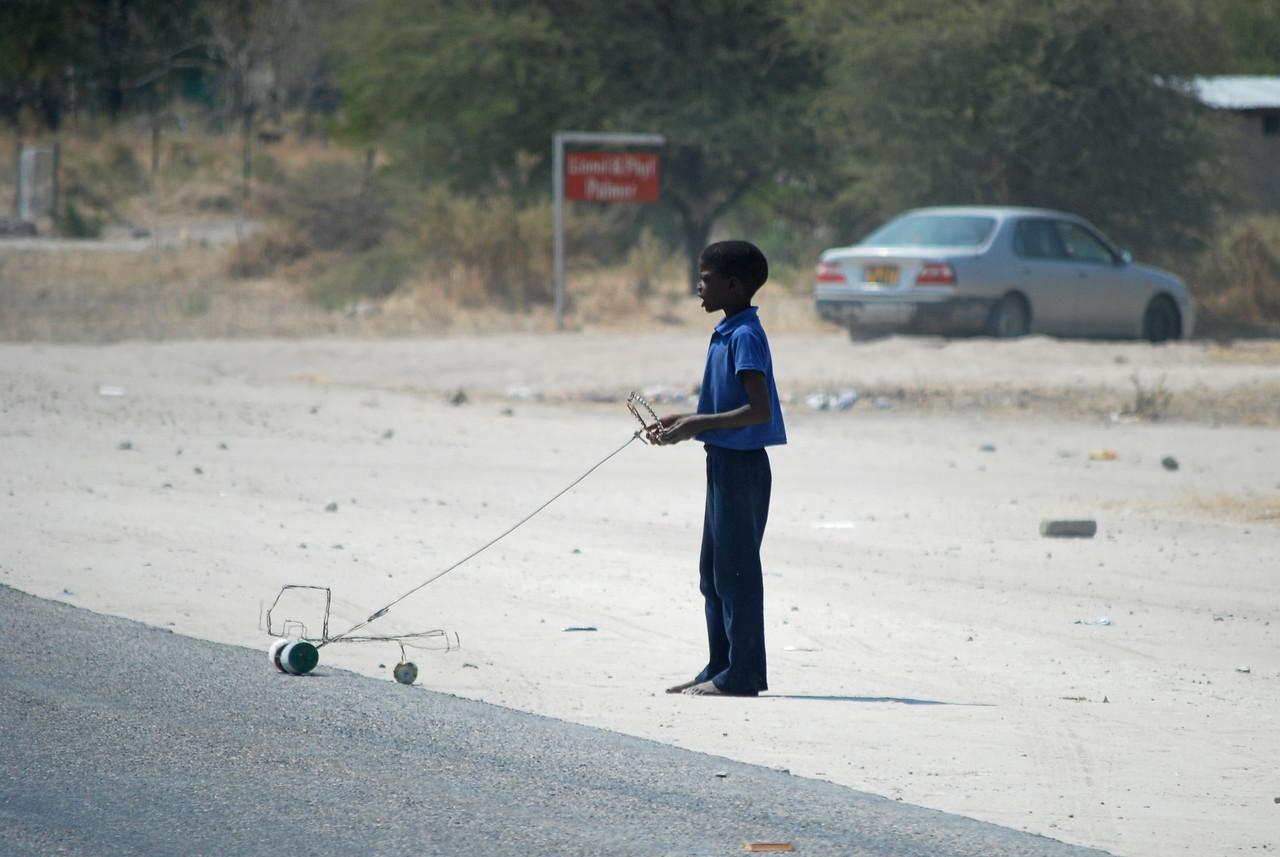 A young boy with a homemade toy beside the highway<br /> <br /> <br /> As we approached Gobabis, we began to encounter people on the highway.