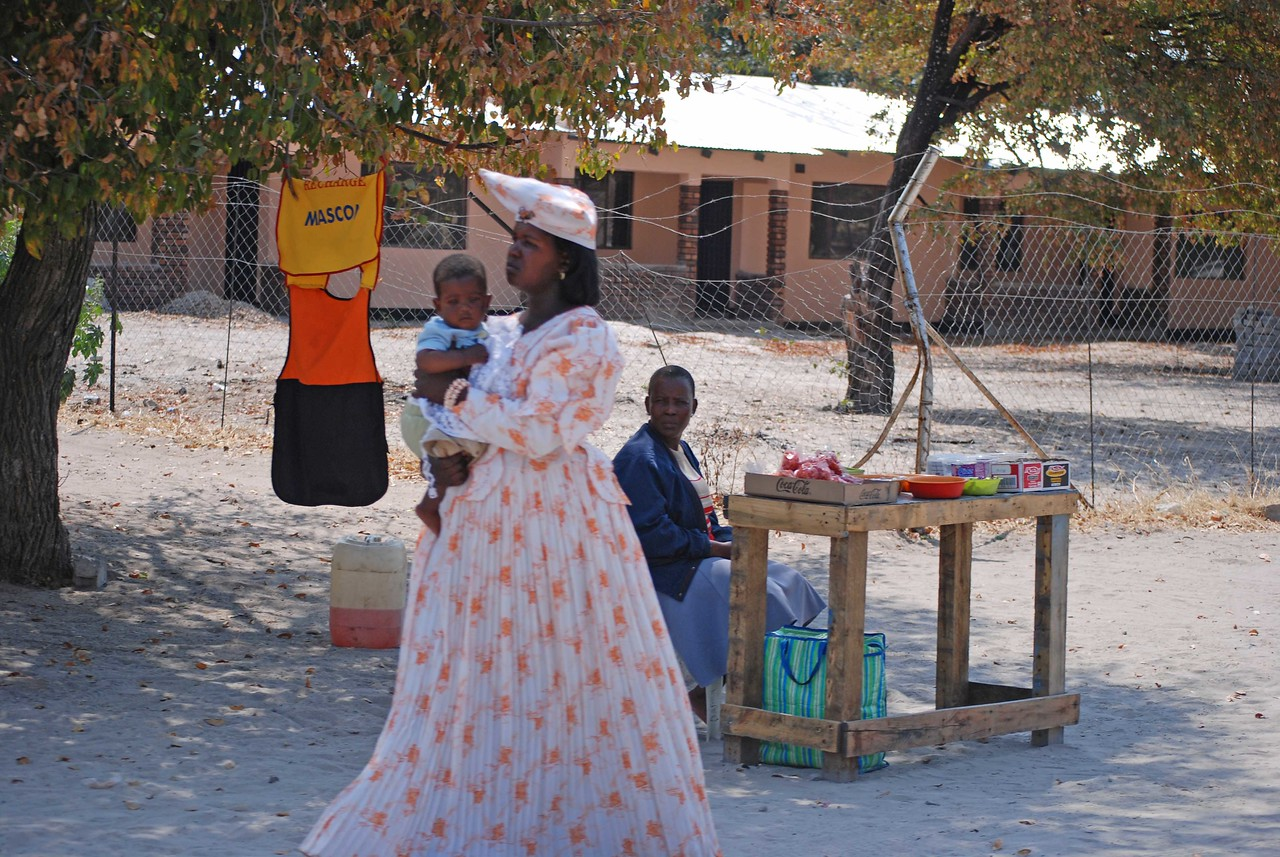 Herero woman in Gobabis<br /> <br /> We drove into Gobabis to top up the tank, not certain when there would be petrol available again. We encountered several Herero women in town, wearing their distinctive, long Victorian gowns and colourful horn-shaped headdresses that remind me somewhat of elongated graduation caps. The hats are said to represent the horns of a cow, which would make sense since the Herero are proud cattle farmers. The Herero live mostly in the central and eastern part of the country, and make up the third largest ethnic group in Namibia, numbering around 100,000. The crinoline and layers of petticoats that the women wear under their Victorian dresses made them look enormous and the men who walked beside them very thin. This impractical style of dress was introduced to the Herero women in the 1800s by missionaries who were shocked at the Herero's semi-nakedness. As I sat in the car in mid-winter, rather warm in my shorts and T-shirt, I couldn't imagine how these women survive the summer temperatures of the Kalahari Desert.