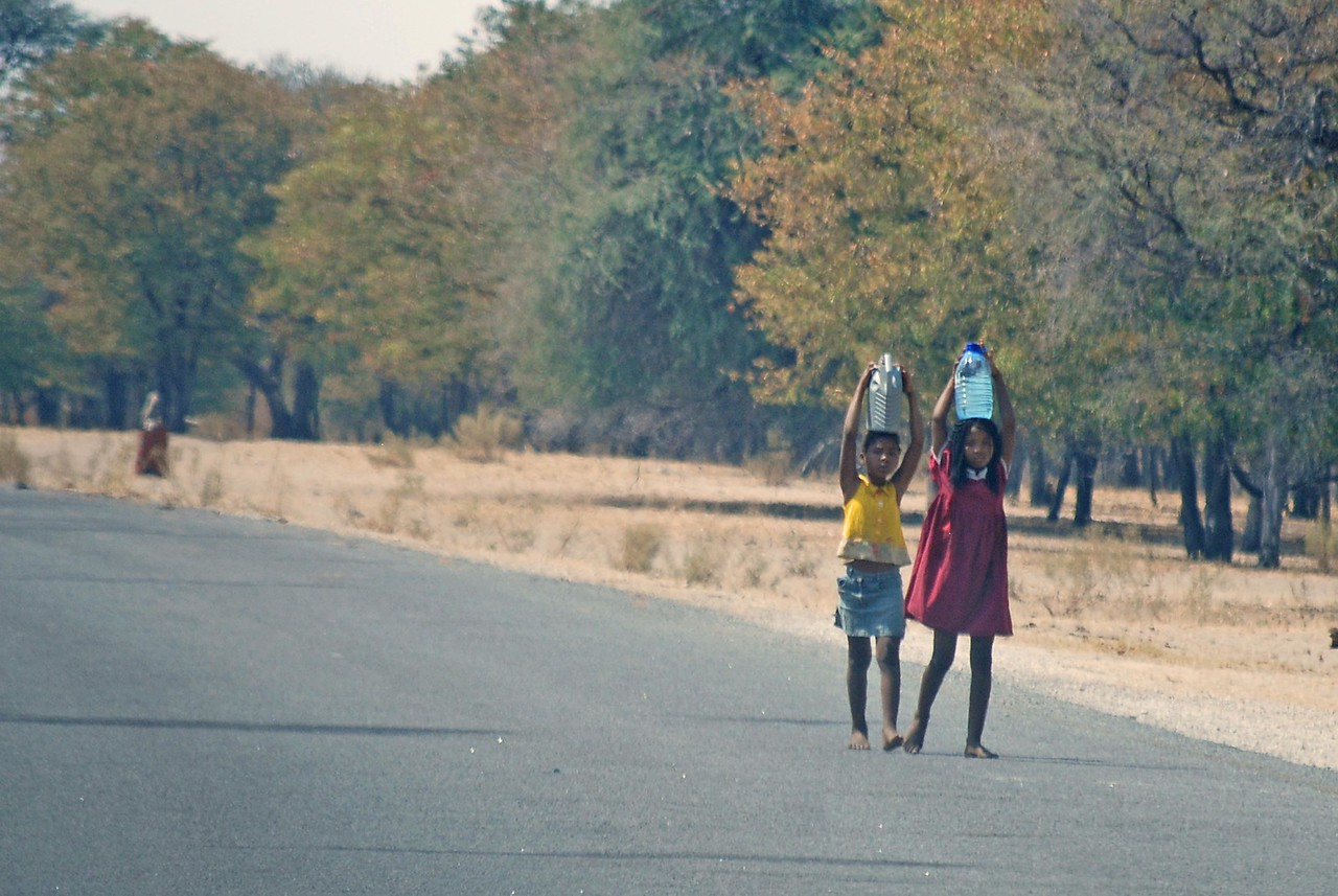 Young girls carrying water along the highway<br /> <br /> Women and children were carrying all manner of things of their heads, but mostly firewood that they had gathered from the nearby bush. It was winter and the nights were cold, often dropping to zero.