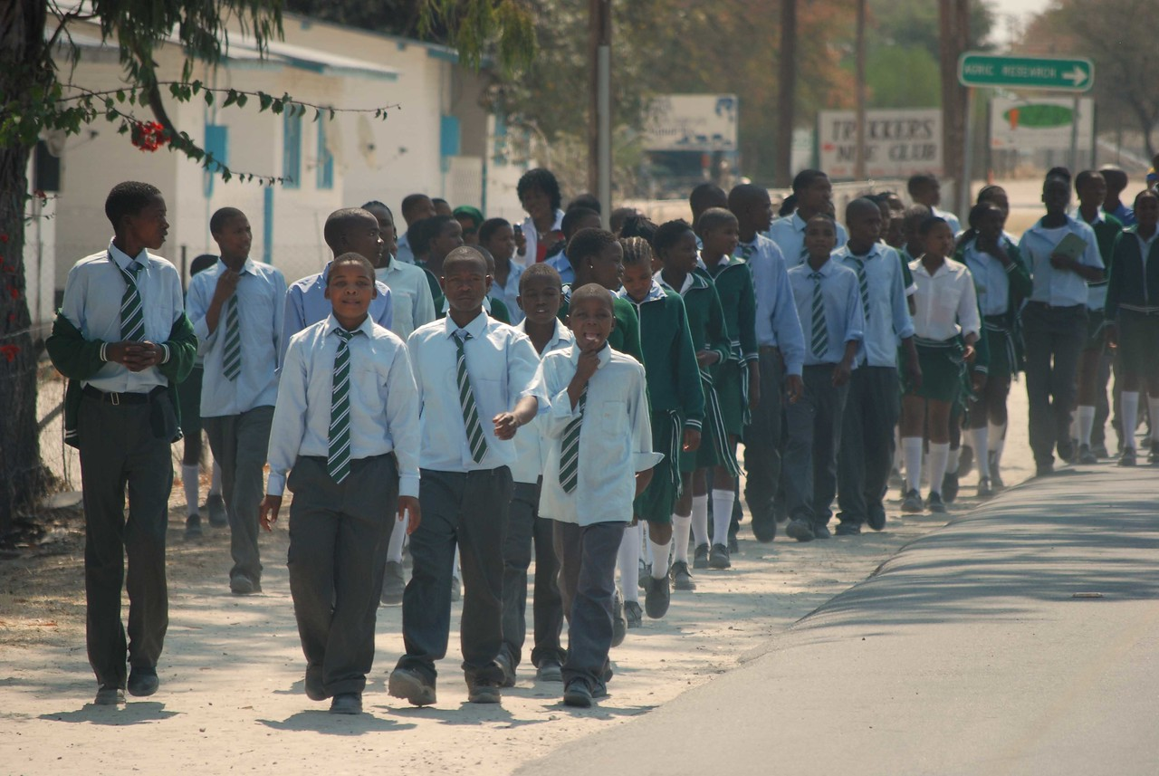School children on Maun's main street<br /> <br /> We arrived in Maun at 11:00am to find a bustling, insanely busy town. Maun is a tourist town and the launch site or finishing point for people heading in or out of the Moremi Game Reserve and Chobe National Park. The Botswana government follows a low-volume, high-cost tourism policy, which means that safaris in Botswana are not cheap. The majority of visitors fly into Maun from Johannesburg, change planes and travel by small aircraft with a safari company from one luxurious safari camp to the next. The cost of this privilege in peak season is about US$800 per person per night, not including the air transfers between camps. <br /> <br /> Self-drivers rent a 4x4 vehicle and utilize the scarce public campsites in the park and reserve - still not cheap by any means and mostly out of the reach of all but international visitors. We like the independence of self-drive, where we are able to determine our own route and set our own pace. While tourists on fly-in safaris see not much more than the Maun airport, self-drivers stay in Maun long enough to stock up on supplies and get organized for their safari. This is what we would be doing for what remained of the day.