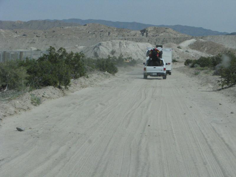 Asphalt turns to a sandy road.