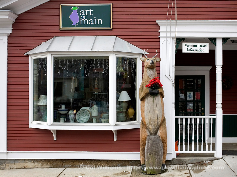 "<b> <center>   <font size = ""3"">     <font color = yellow>  The Deerleap Deer      </font color=yellow>   </font size = ""3""> </center>    <font size = ""2"">     <font color=white>  <br> This wooden deer, carved by Kate Earley, guarded the door of Deerleap Bookstore as mascot/signpost.  When Art on Main Gallery took over the space, the deer stayed on the job. <br>      </font color = white>   </font size = ""2"">"