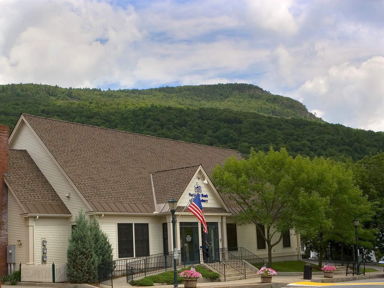 "<b> <center>   <font size = ""3"">     <font color = yellow>  Bristol Branch, Bank of Middlebury       </font color=yellow>   </font size = ""3""> </center>    <font size = ""2"">     <font color=white>  <br> Deerleap Mountain looms over the Bristol Branch of the National Bank of Middlebury, on Main Street.  The Deerleap Vista cliffs can be seen near the left side. <br>      </font color = white>   </font size = ""2"">"
