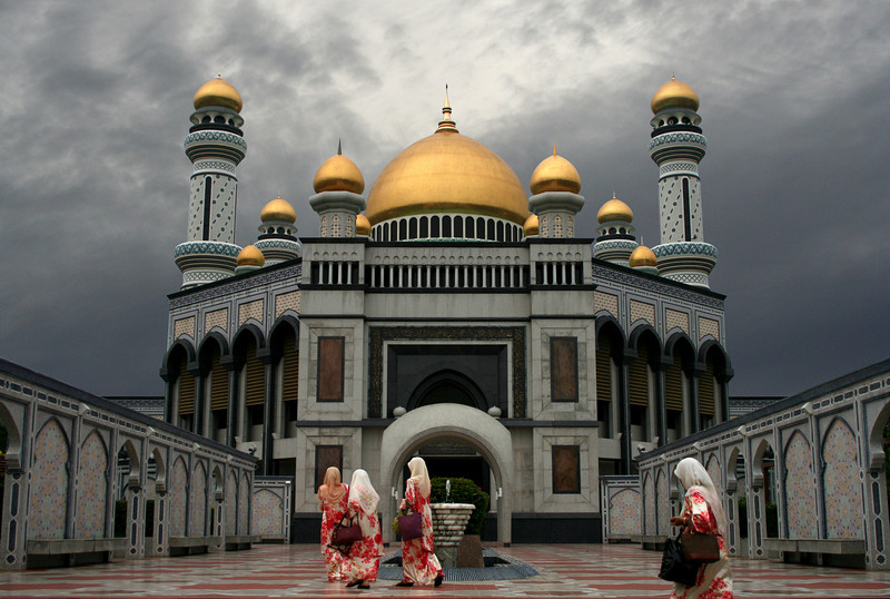"Hassanal Bolkiah Mosque is the largest in Brunei and was built in 1992 to commemorate the Sultan's 25th anniversary on the throne. A lavish building inspired by the Dome of the Rock and the Alhambra, it features 29 onion domes - a reminder that the present Sultan is the 29th in his line to rule Brunei. Each dome is covered in a centimetre-thick layer of solid gold tiles. The mosque was designed by an Australian architect who fell to his death from scaffolding during construction, and - according to the tour guide - ""burst like a tomato""."